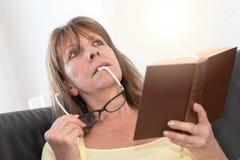 Заботливая женщина держа ее стекла и читая книгу Стоковые Изображения
