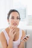 Заботливая женщина при мобильный телефон сидя на софе Стоковые Изображения RF