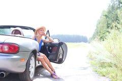 Заботливая женщина сидя в автомобиле с откидным верхом на проселочной дороге против ясного неба Стоковое фото RF