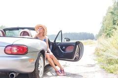 Заботливая женщина сидя в автомобиле с откидным верхом на проселочной дороге против ясного неба Стоковые Изображения
