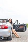 Заботливая женщина сидя в автомобиле с откидным верхом на проселочной дороге против ясного неба Стоковая Фотография RF
