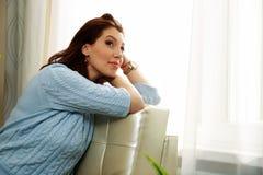 Заботливая женщина сидя на софе Стоковое Фото