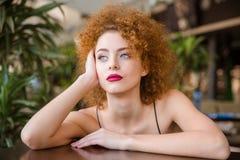 Заботливая женщина сидя на таблице в ресторане Стоковые Фото