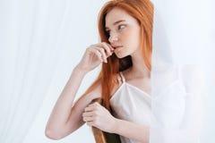 Заботливая женщина redhead смотря прочь стоковые фото