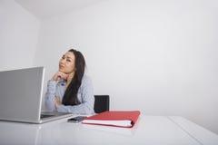 Заботливая коммерсантка сидя на столе офиса Стоковое Фото