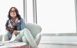 Заботливая коммерсантка сидя на таблице в творческом офисе Стоковые Изображения