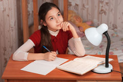 Заботливая девушка делая домашнюю работу на таблице Стоковое Изображение