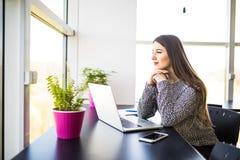 Заботливая милая женщина офиса сидя на ее столе при компьтер-книжка, смотря в расстояние с рукой на ее подбородке стоковое фото rf