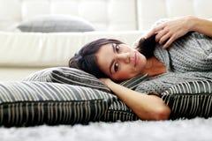 Заботливая молодая женщина лежа на поле с подушками Стоковые Изображения RF