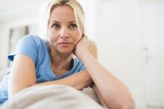 Заботливая молодая женщина сидя в живущей комнате Стоковые Фото