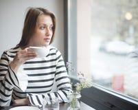 Заботливая молодая женщина смотря вне от окна пока выпивающ кофе в кафе Стоковые Изображения
