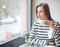 Заботливая молодая женщина смотря вне от окна пока выпивающ кофе в кафе Стоковая Фотография RF