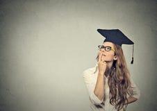 Заботливая постдипломная молодая женщина градуированного студента в мантии крышки смотря вверх думающ Стоковые Изображения RF