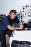 Заботливая склонность механика на автомобиле с открытым клобуком Стоковые Фото