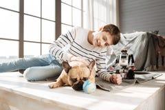 Заботливая собака лежа около его молодого мастера Стоковое Фото