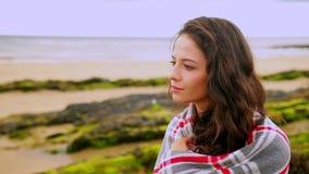 Заботливое брюнет обернутое в одеяле сидя пляжем сток-видео