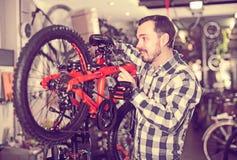 Заботливые мужские части велосипеда держателей для собрания велосипед в магазине Стоковая Фотография RF