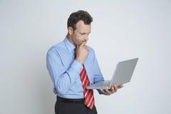 Заботливый бизнесмен используя компьтер-книжку стоковые фото