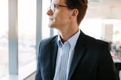 Заботливый бизнесмен стоя в офисе Стоковые Изображения
