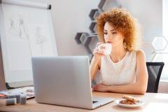 Заботливый милый фотограф женщины работая с компьтер-книжкой и выпивая кофе Стоковое Изображение RF