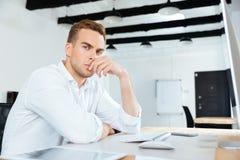Заботливый молодой бизнесмен работая с компьютером в офисе Стоковые Изображения