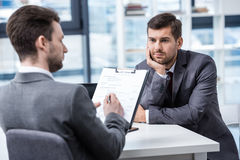 Заботливый молодой бизнесмен смотря менеджера с доской сзажимом для бумаги на собеседовании для приема на работу Стоковое Фото