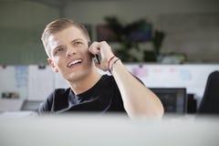 Заботливый молодой человек смотря отсутствующий пока использующ сотовый телефон на офисе Стоковые Фотографии RF