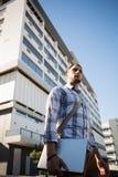 Заботливый молодой человек смотря отсутствующий пока стоящ на улице города Стоковая Фотография
