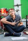 Заботливый профессионал держа Drumsticks пока сидящ на Floo стоковая фотография