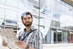 Заботливый человек смотря отсутствующий пока держащ дорожную карту против стеклянной стены Стоковые Фотографии RF