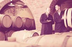 2 заботливых люд в формах принимая примечания в погребе с вином Стоковое фото RF