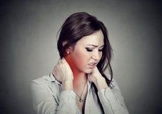 Заболевание позвоночника Женщина массажируя тягостную шею покрашенную в красном цвете стоковое фото