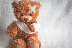 Заболевания детства плюшевого медвежонка концепции на предпосылке ткани стоковая фотография