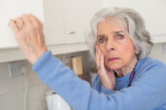 Забывчивая старшая женщина при слабоумие смотря в кухонном шкафе Стоковая Фотография