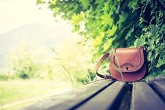 Забытая кожаная сумка на скамейке в парке, никто стоковое фото