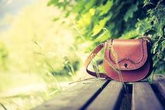 Забытая кожаная сумка на скамейке в парке, никто стоковые изображения rf