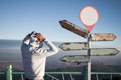 заблудившийся человек в положении сомнения и смущенный перед пустым guid Стоковые Фото