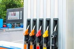 Завалка бензина, взгляд бензоколонки и пистолетов с топливом для автомобилей, цена табло и количество топлива Концепция co стоковая фотография
