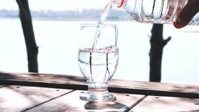 Завалка воды в стекле в природе сток-видео