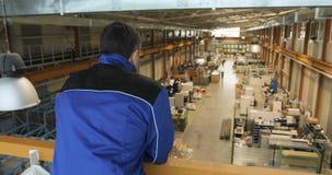 Заведущая или работник обозревают продукцию большой фабрики акции видеоматериалы