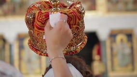 Заверители держат золотую крону над новобрачными сток-видео