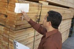 Заведущая проверяя ярлык на стоге древесины Стоковое Фото