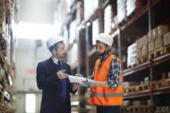Заведущая склада разговаривая с построителем заказа стоковое изображение