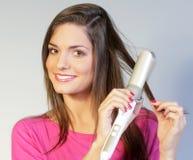 завивая волосы девушки она Стоковая Фотография RF