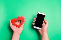 Зависимость на социальных сетях smartphone и сердце телефона в руках онлайн датировка, flirting, сообщение и вызывая ваше полюбле стоковые фотографии rf
