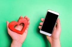 Зависимость на социальных сетях smartphone и сердце телефона в руках онлайн датировка, flirting, сообщение и вызывая ваше полюбле стоковые фото