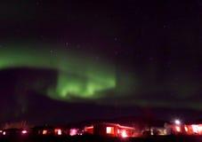Завихряясь северное сияние над маленьким городом в Исландии стоковая фотография rf