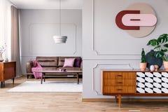 Заводы на деревянном кухонном шкафе в интерьере открытого пространства с settee плаката и кожи с одеялом Реальное фото стоковое фото rf