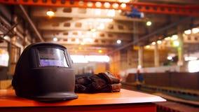 Завод конструкции Люди работая на предпосылке Кран двигает детали Черный шлем и защитные перчатки дальше стоковые фото