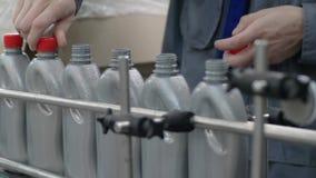 Завод масла машины, работника закрывает крышки на серых пластиковых бутылках двигая на линию конец транспортера вверх сток-видео